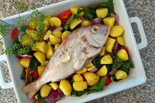 casserole with fresh gilthead sea bream with vegetable and herbs as top view. Raw dorado fish with spices and vegetables on the table. Diet vegetarian food. Dorado Royale Fish