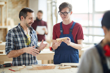 Waist up portrait of mature carpenter talking to smiling young apprentice in workshop, copy space