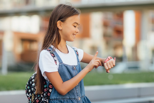 Technology for children, a girl wearing jeans dress uses a smartwatch on fresh air. Lifestyle.