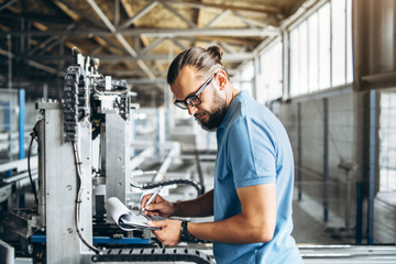 Fototapeta Young engeneer manager with beard checking manufactory, workplace and machinery on big factory. obraz