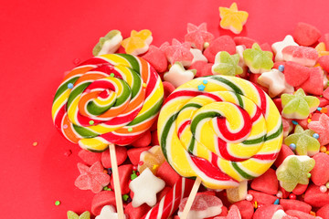 Fotobehang Roze Assorted colorful gummy candies and lollipop on red background. Top view. Jelly sweets.