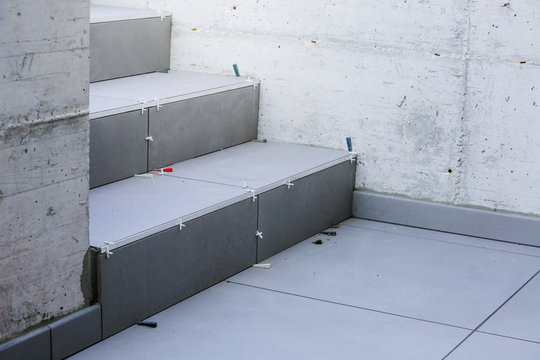 Laying new tiles on a concrete steps outside of a building