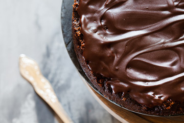 Chocolate brownie cake with ganashe topping on gray background