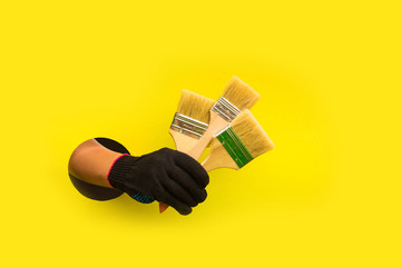 Construction tool in the hand of a girl. Symbol of hard work, feminism and work day. In the Hole on a yellow background, the concept of a happy labor day