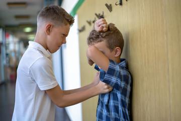 Boy bully   Bullying  classmate in school hallway.
