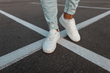 Close-up of male legs. Fashionable young man stands on the asphalt road in leather stylish white...
