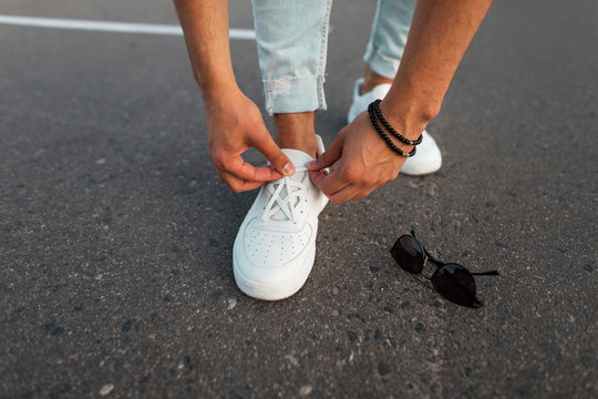 Young stylish man in blue jeans in leather white trendy shoes stands on the road next to sunglasses and straightens shoelaces. Fashionable mens sneakers and accessories. Close-up.