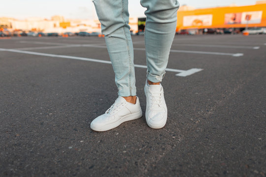 Fashionable modern young man in stylish blue jeans in a trendy leather seasonal white sneakers stands in a parking lot in the city. Closeup of men's stylish legs. Summer look.