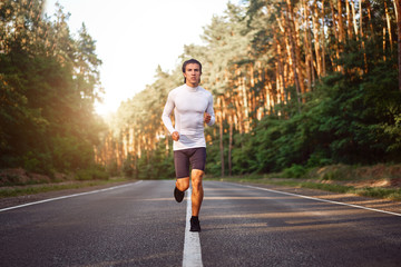 Caucasian middle age man athlete runs sunny summer day on asphalt road in the forest.