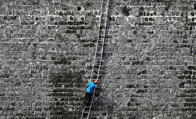 A worker cleans a wall at the Jaffna Fort, a fort built by the Portuguese in 1618, in Jaffna