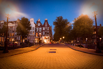 Wall Mural - Street scene in Amsterdam at night with lights and architecture