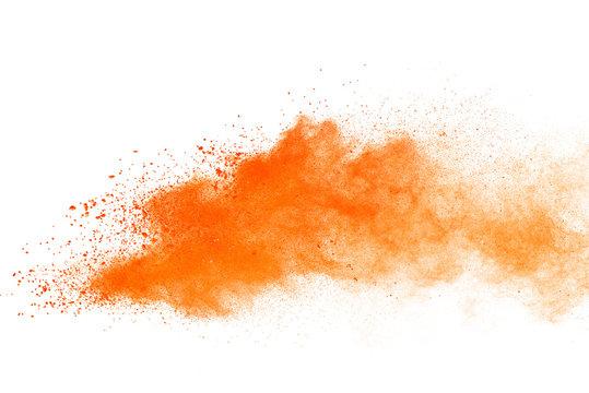 Abstract orange powder explosion. Closeup of orange dust particle splash isolated on white background