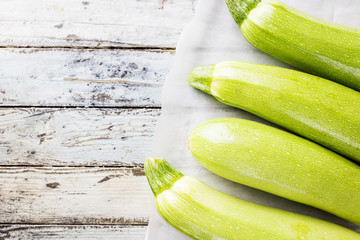 Fresh organic summer vegetables zucchini on rustic wooden background. Top view, space for text.