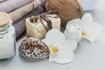 Organic cosmetics with coconut oil, sea salt, towels and handmade soap with white orchid flowers on grey background