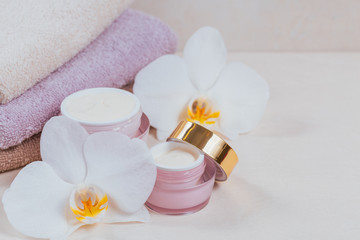 Bottles of hand or face cream or facial mask, towels and white orchid flowers on light background.