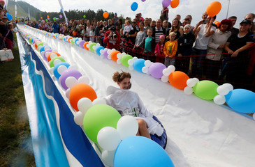A participant slides down along a chute to cross a pool of water and foam during the festival near Krasnoyarsk