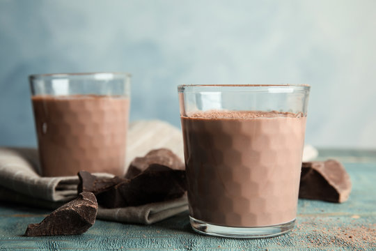 Glasses with tasty chocolate milk on wooden table. Dairy drink