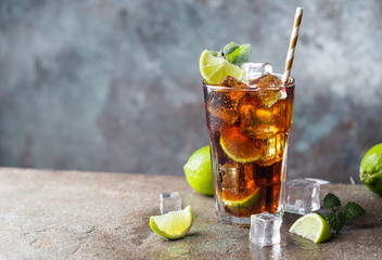 Fototapeta Fresh made Cuba Libre with brown rum, cola, mint and lemon on gray stone background