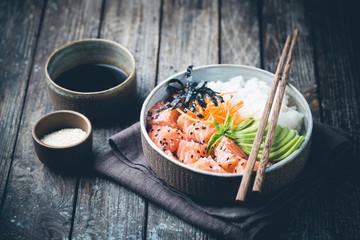 Hawaiian salmon poke bowl with seaweed, avocado, carrot, sesame seeds and rice.