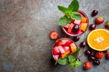 Red wine sangria or punch with fruits and ice in glasses top view. Homemade refreshing fruit sangria.