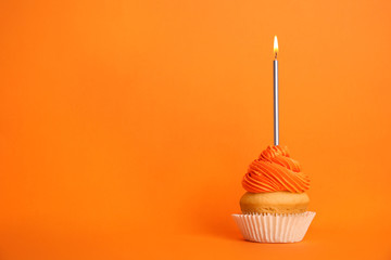 Birthday cupcake with candle on orange background, space for text