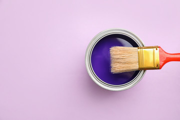 Open can with blue paint and brush on lilac background, top view. Space for text Wall mural