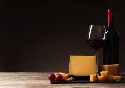 Delicious cheese served with red wine on table against dark background. Space for text
