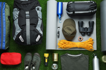 Flat lay composition with different camping equipment on green grass