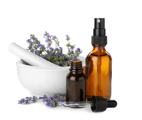 Bottles of essential oil, mortar and pestle with lavender flowers isolated on white