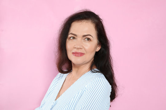 Portrait of mature woman with beautiful face on pink background