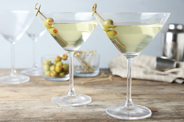 Spoed Foto op Canvas Alcohol Glasses of Classic Dry Martini with olives on wooden table against grey background