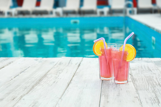 Refreshing cocktails near outdoor swimming pool on sunny day