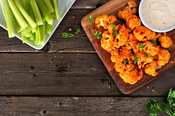 Cauliflower buffalo wings. Top view table scene against a wood background with copy space. Healthy eating, plant based meat substitute concept.