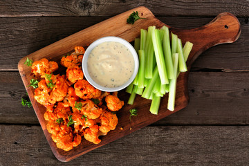 Photo sur Aluminium Buffalo Cauliflower buffalo wings with celery and ranch dip. Top view on a wood paddle board. Healthy eating, plant based meat substitute concept.