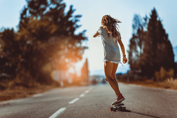 Young sporty woman riding on the skateboard on the road.