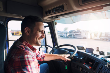 Professional middle aged truck driver in casual clothes driving truck vehicle going for a long...