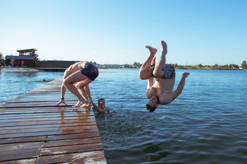 friends jumping from wooden pier in water