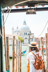 woman in white clothes with straw hat at pier basilica santa maria della salute on background