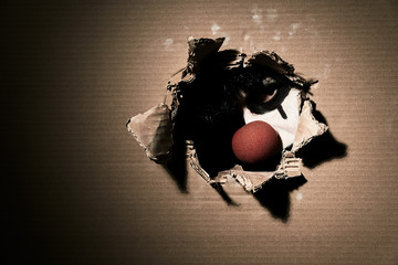 A creepy scary vampire clown with a red nose looks through a torn cardboard. Halloween theme with blank space on the left.