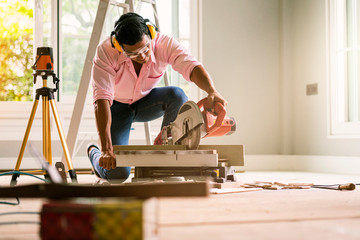 smart indian contractor hand use sawing machine wood work house renovation background home...