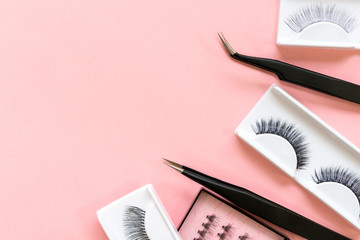Tools for eyelash extension on trendy pastel pink background. False eyelashes and tweezers. Beauty shop. Makeup cosmetics. Top view, flat lay. Place for text