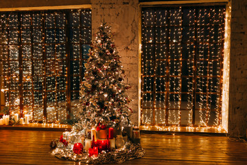 warm cozy magic evening in luxury old Christmas living room fairy tale interior design,pahoramic windows, Xmas tree decorated by lights,gifts, candles, lanterns, garland lighting.New year holidays