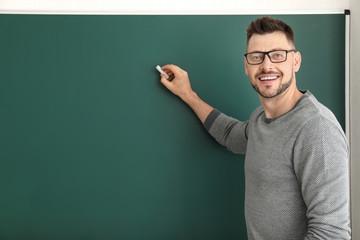 Male teacher writing on blackboard in classroom