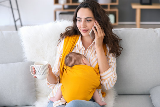 Young mother with little baby in sling talking by mobile phone at home