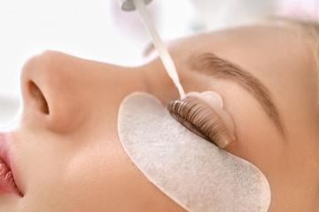 Obraz Young woman undergoing procedure of eyelashes lamination in beauty salon, closeup - fototapety do salonu
