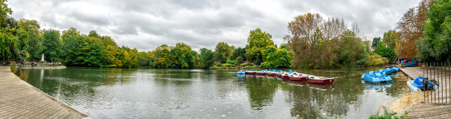 Panoramic view of a boating lake with paddle boats parked and park cafe outdoor tables, Battersea Park, London