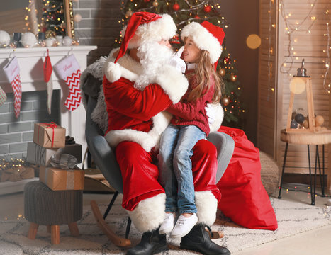 Santa Claus and little girl in room decorated for Christmas