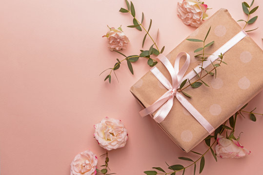Gift box and beautiful flowers on color background