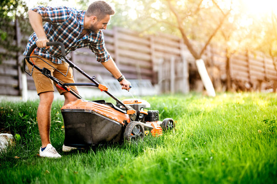 Gardening details, garden worker starting the lawnmower and cutting grass in garden.