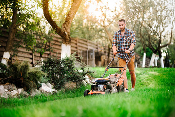 Close up details of landscaping and gardening. Worker using industrial manual lawnmower.
